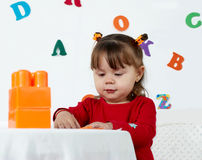 Little girl plays a colorful cubes Stock Photo