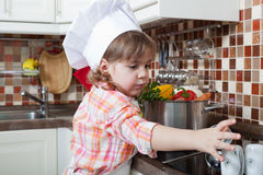 Little girl plays the cook Stock Photography