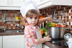 Little girl plays the cook Stock Photos