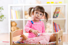 Little girl plays doctor examining a doll patient Royalty Free Stock Images