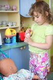 Little girl plays with doll on kitchen Stock Photography