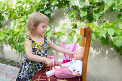 A little girl plays with dolls Stock Photos