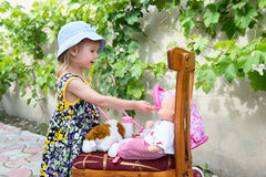 A little girl plays with dolls Stock Photo