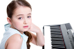 Little girl plays on the electric piano. Royalty Free Stock Images