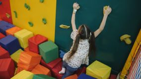 Little girl plays in an entertainment trampoline center. child rolls cubes of foam rubber. Girl playing with soft cubes stock footage