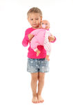 Little girl plays with favorite doll Stock Images