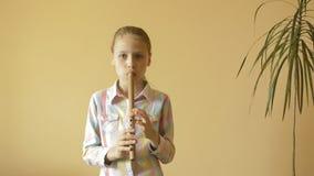 Little girl plays flute stock video