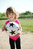 Little girl plays football on stadium Royalty Free Stock Photo