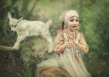 A little girl plays in the forest with a goat