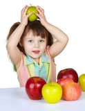 Little girl plays with fruit - apples Royalty Free Stock Images