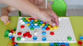 A little girl plays a game, works out a multi-colored mosaic that develops, developing motor skills and thinking in stock footage