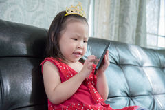 Little girl plays games on smart phone Stock Photography