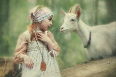 A little girl plays with a goat in the village in the summer in the forest