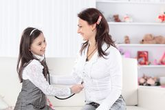 Little girl plays with her mother in the doctor royalty free stock photos