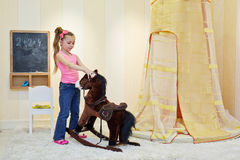 Little girl plays with hobbyhorse Stock Image