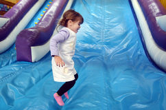 Little girl plays on Inflatable giant slide Stock Photos
