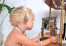 Little girl plays with jewelry Stock Images