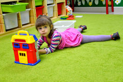 The little girl plays in kindergarten, lying on a floor Stock Photo