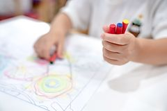 Little girl plays and learns to coloring Crayon on the paper in the ice-cream restaurant., Bangkok, Thailand. Little girl plays and learns to coloring Crayon  on royalty free stock image