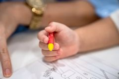 Little girl plays and learns to coloring Crayon on the paper in the ice-cream restaurant., Bangkok, Thailand stock images