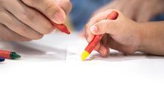 Little girl plays and learns to coloring Crayon on the paper in the ice-cream restaurant., Bangkok, Thailand royalty free stock images