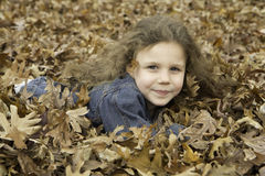 Little Girl Plays in Leaves 1 Stock Image