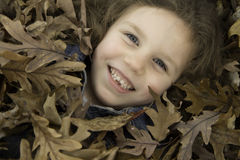 Little Girl Plays in Leaves 2 Stock Photography