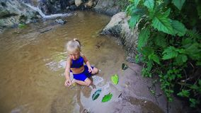 Little Girl Plays with Leaves in Pond Shallow Water stock footage