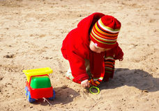 Little girl plays with the machine. In sand Royalty Free Stock Photo