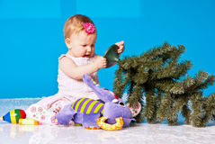 Little girl plays with New Year tree Royalty Free Stock Photo