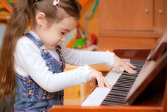 Little girl plays piano. Small dark-haired girl plays piano in educational class Royalty Free Stock Photos