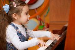 Little girl plays piano. Small dark-haired girl plays piano in educational class Royalty Free Stock Images