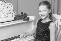 Little girl plays the piano, black and white photo. Beautiful little girl is playing the piano, retro style, black and white photo in the studio. The concept of Royalty Free Stock Photography