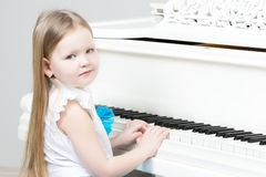 Little girl plays the piano. Stock Images