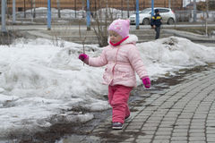 The little girl plays on the playground in the spring. Stock Image