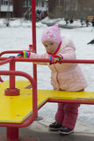 The little girl plays on the playground in the spring. Stock Photography