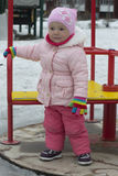 The little girl plays on the playground in the spring. Royalty Free Stock Image