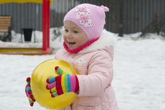 The little girl plays on the playground in the spring. Royalty Free Stock Photos