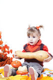 Little girl plays with  pumpkins Stock Image