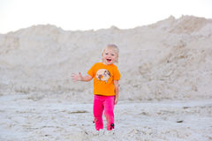 Little girl plays in the sand and looking at the camera Royalty Free Stock Photo