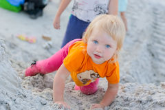 Little girl plays in the sand and looking at the camera Royalty Free Stock Photography