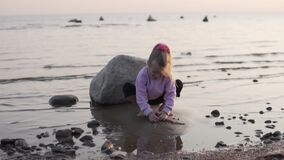 A little girl plays in the sand by the sea on the autumn beach of the Baltic Sea