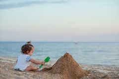 A little girl plays on a sandy beach with a shovel and a bucket. royalty free stock photography