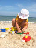Little girl plays at the sea. Little girl plays on the sand at the sea Royalty Free Stock Photo