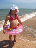 Little girl plays at the sea Stock Photography