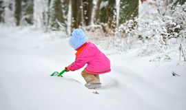 Little girl plays with a shovel in the snow Stock Photography