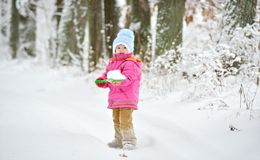 Little girl plays with a shovel in the snow Royalty Free Stock Photography