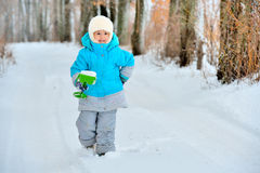 Little girl plays with a shovel in the snow Royalty Free Stock Image