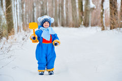 Little girl plays with a shovel in snow Stock Images