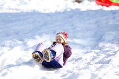 Little girl plays with sledding on snow Royalty Free Stock Image